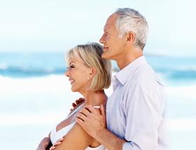 Couple âgé enlacé à la plage